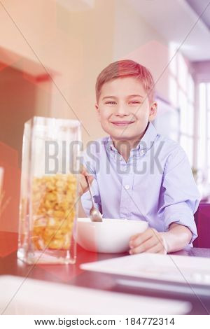Portrait of smiling boy pouring corn flakes in bowl at home