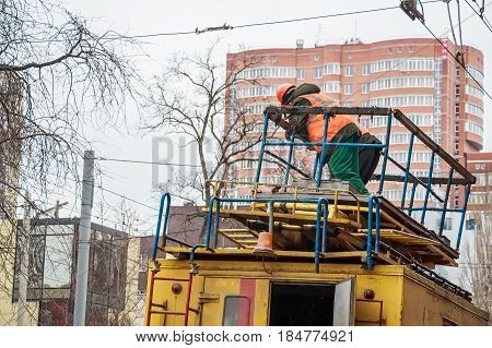 Close up man in uniform standing on top of yellow Russian ectrical emergency service truck