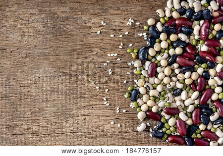 mix of beans on wood table. green bean soybean black bean red bean and White kidney bean