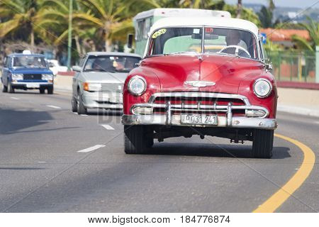 HAVANA,CUBA-JANUARY 10, 2017: Old vintage car moving in urban city street during day. Cuba is well known for the vast array of obsolete mode of transportation still running.