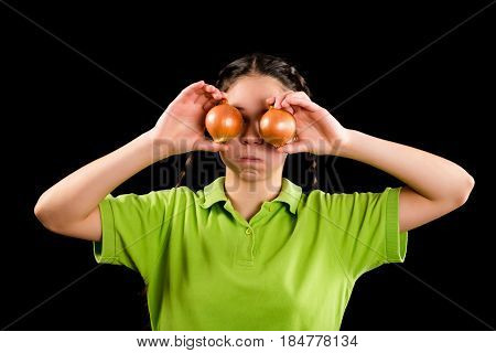 funny girl with yellow onion bulbs on eyes on black background