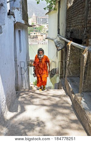 INDIA, LAXMAN JHULA - APRIL 15, 2017: Sadhu coming from the river Ganges after doing puja in Laxman Jhula on the 15th of april 2017