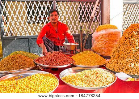 INDIA, LAXMAN JHULA - APRIL 8, 2017: Seller selling all kinds of indian food in the streets of Laxman Jhula on the 8th of april 2017