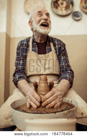 Front View Of Male Craftsman Working On Potters Wheel