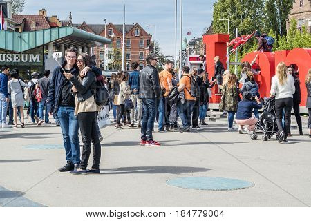 AMSTERDAM , NETHERLANDS - APRIL 31, 2017 : Couple taking selfies while people walking around the I Amsterdam letters in the square in front of museumplein