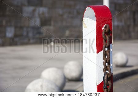 Photo of a bollard of red and white colour with sunlight