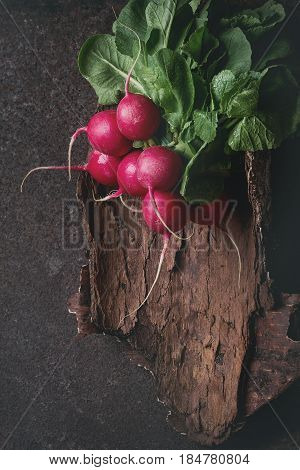 Fresh organic ripe young radish bundle with leaves on wooden bark over dark metal texture background. Top view with space