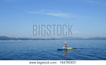 Kayak. People kayaking in the beautiful lake. Leisure activities on the calm blue water.