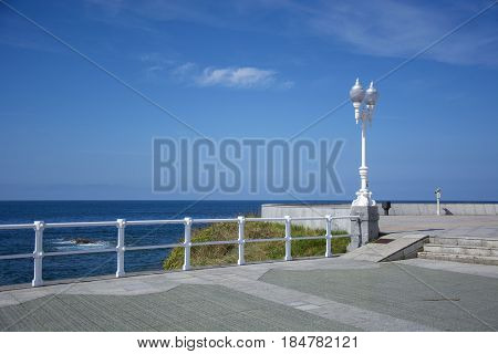 Photo of a streetlight with blue sky, white railing and sunlight