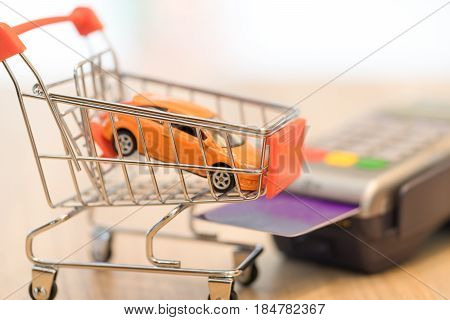 Concept of buying new car by money with red shopping cart and magnetic card