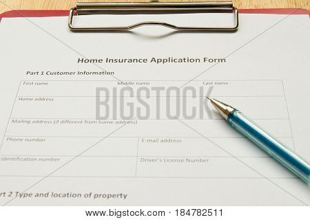 Home insurance application form with red file on wooden table