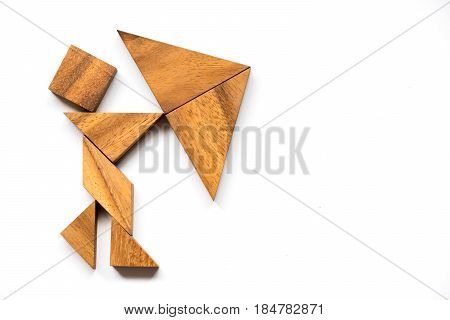Wooden tangram as man hold umbrella shape on white background (Concept as business has the crisis)