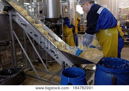ST. PETERSBURG, RUSSIA - FEBRUARY 28, 2017: Worker at the conveyor with pickled cabbage in the Factory of Homemade Pickles. The company participates in the regional quality certification program
