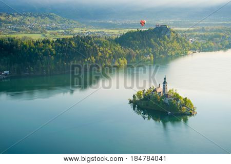 Aerial view of Lake Bled at sunny spring morning with Bled island on foreground and colorful balloon on background Slovenia