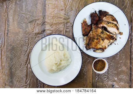 Grilled chicken and sticky rice on wooden background