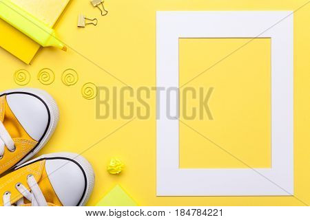 Back to school concept. School accessories with white frame on yellow background. Flat lay. Copy space. Top view