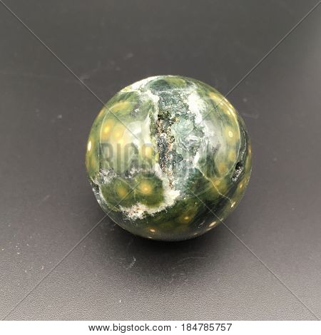 an interesting green crystal that has been shaped into a perfect orb