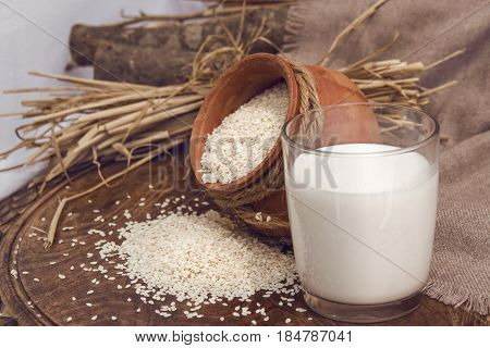 Vegan sesame milk in glass and white sesame seeds in a clay pot on a wooden table. Raw food diet. Horizontal photo without people for catalog, menu, billboards, banner.