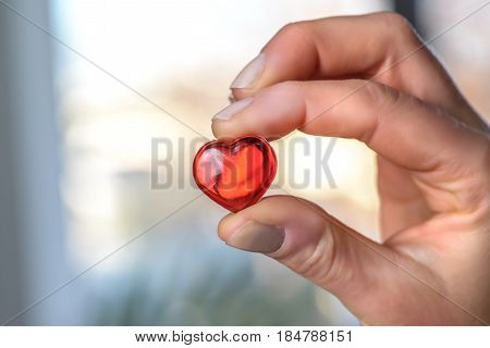 Close up of a woman hand holding a red heart