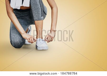 Closeup of Asian woman tying shoelaces and getting ready for running on city road Female sport finess