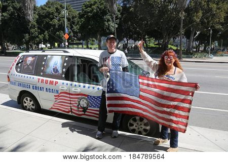 LOS ANGELES California- May 1, 2017: People Wave Signs, Wear Costumes, Yell, Smile and Support President Trump at a Protest Rally Against President Donald J. Trump on May 1, 2017 in Los Angeles.
