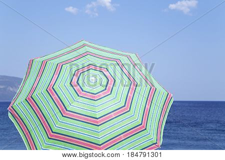The green sunshade over a blue sea
