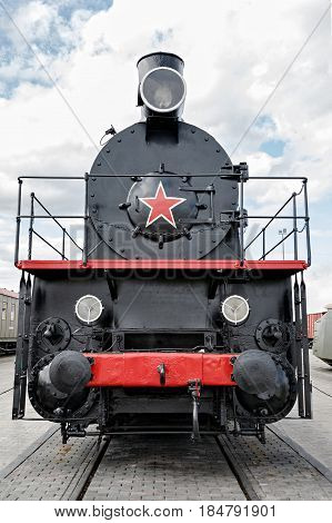 Black steam engine. The locomotive on the railroad. Ahead of red star. The train is ready to move forward. Retro locomotive black. Cloudy sky.