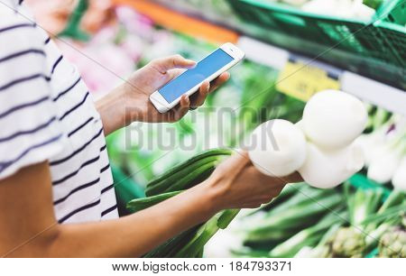 Young woman shopping healthy food in supermarket blur background. Female hands buy onion products and using smart phone in store. Hipster at grocery holding basket. Person comparing price of produce