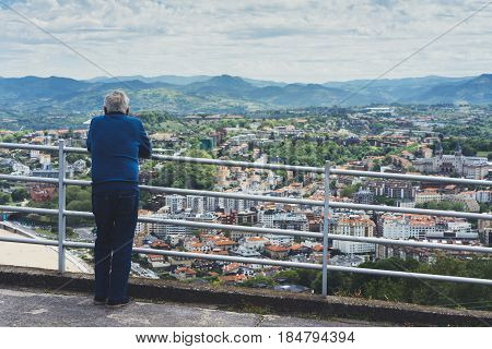 Elderly old man looking on observation deck in trip holiday in Bilbao pensioner enjoying view on seascape on mountain and ocean tourist traveler on background panoramic view of the city. Mock up for text