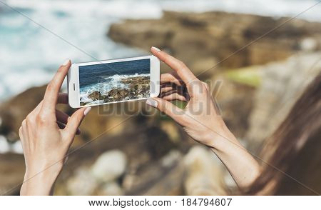 Hipster photograph on smart phone gadget mobile mock up of blank screen. Traveler hold and using in female hand mobile on background mountain seascape horizon. Tourist look on blue ocean lifestyle