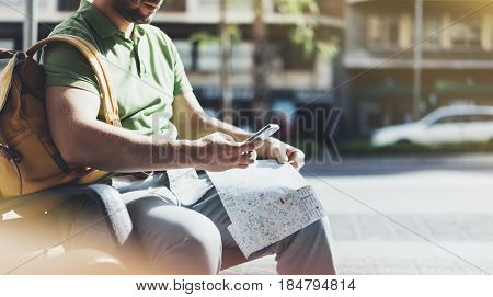 Man with yellow backpack holding smartphone tourist looking map city on background taxi hipster planning route using in hands mobile phone traveler connect wifi internet backdrop summer street mockup