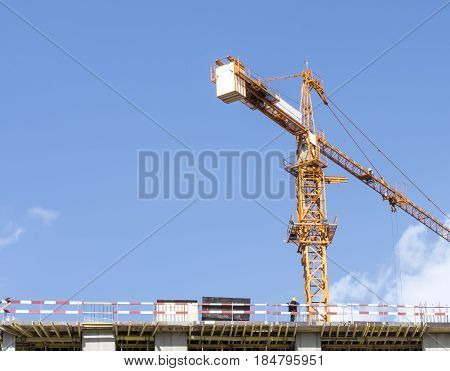 Building cranes on construction site with builders. Tower Crane Hook and Building Constructors on Construction Site.