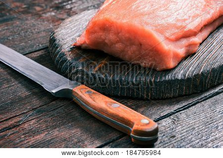 Raw pork meat loin on rustic wooden cutting board and chefs knife on old dark wood table. Close-up angle view