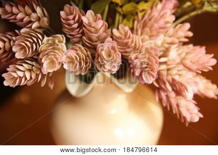 Ornamental plants cones hops in a pink vase stylized as postcards mid-twentieth century.