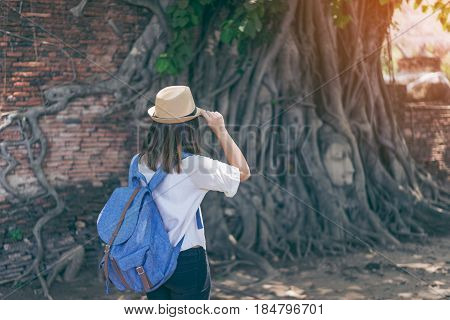 Young woman traveler with backpack and hat looking the Head of the Buddha with tree trunk and roots growing around it. Wat Mahathat temple Ayutthaya near Bangkok Thailand. Traveling in Ayutthaya