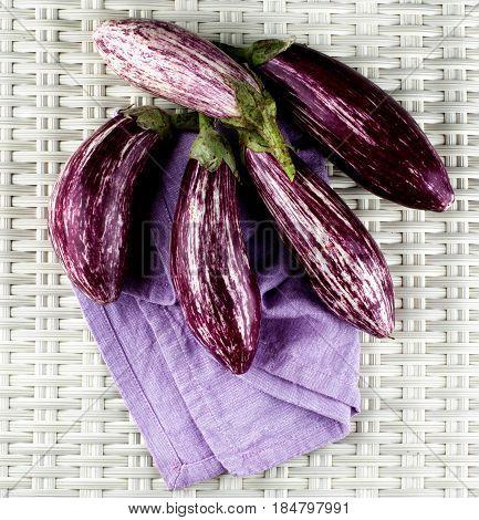 Stack of Fresh Raw Striped Eggplants on Purple Napkin closeup on Wicker background