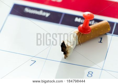 Cigarette butt impaled on calendar with first day of the month