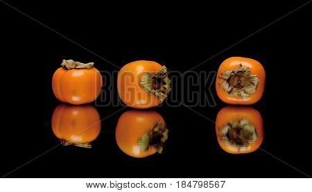 Ripe persimmon on a black background with reflection. Horizontal photo.