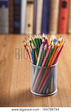 Wire desk tidy full of coloured pencils standing on a wooden table in front of a bookshelf full of books with shallow dof and copyspace