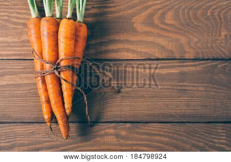 Bunch of young carrots with green tops on wooden vintage table healthy food on mock up background top view diet and vegetarian orange vegetable; vitamin agriculture concept