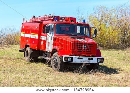 Samara Russia - April 30 2017: Red fire truck EMERCOM of Russia parked up on the spring field