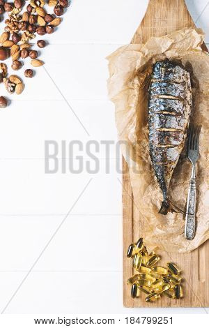 Baked fish with nuts and fish oil capsules on parchment paper and cutting board on a white background of the old wooden boards vintage top view vertical seafood on table kitchen