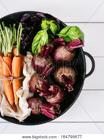 Bunch of young carrots beets and basil on a white background of the old wooden boards vintage fresh vegetable on backdrop kitchen table top view healthy vitamin vegan food organic nature plant in garden dieting concept mock up