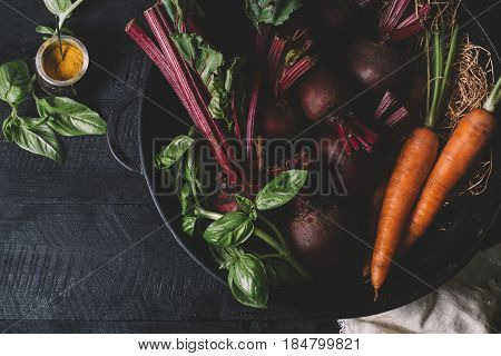 Bunch of young green onions beets carrots and basil on a black background of old wooden boards vintage fresh beetroot vegetable on backdrop kitchen table top view healthy vitamin vegan food organic nature plant in garden dieting concept mock up