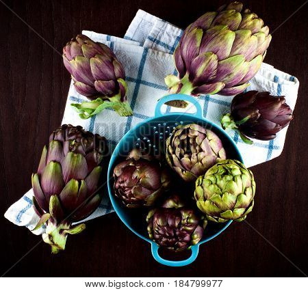 Stack of Perfect Raw Artichokes in Blue Colander closeup on Checkered Napkin closeup on Dark Wooden background. Top View