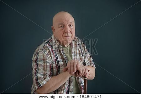 Senior man with cane on dark background. Poverty concept