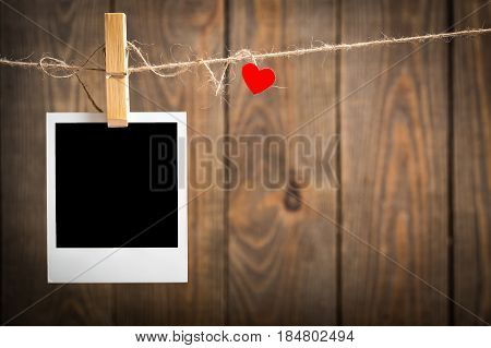 Blank instant photo and small red paper heart hanging on the clothesline. On old wood background