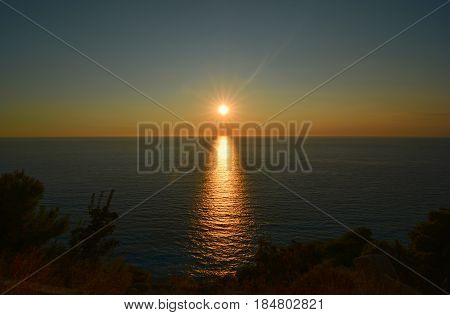 Sunset over the sea dark blue clear sky horizon and dark sea surface with sunset reflection