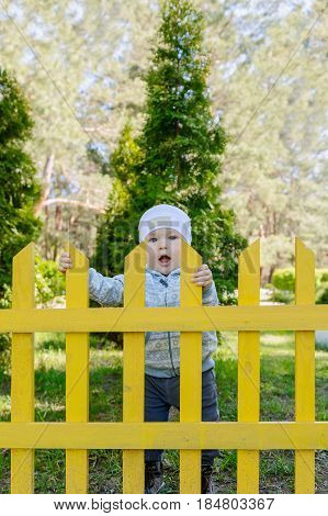 A small boy stands behind the yellow fence