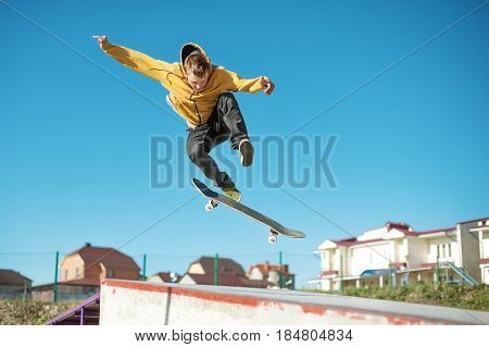 A teenager skateboarder does an flip trick in a skatepark on the outskirts of the city On a background of houses and a blue sky